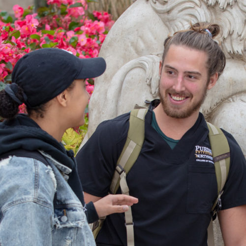 Students talk together on campus.