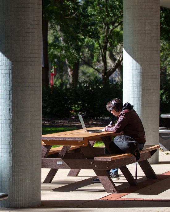 Student sitting on bench with laptop and headphone one