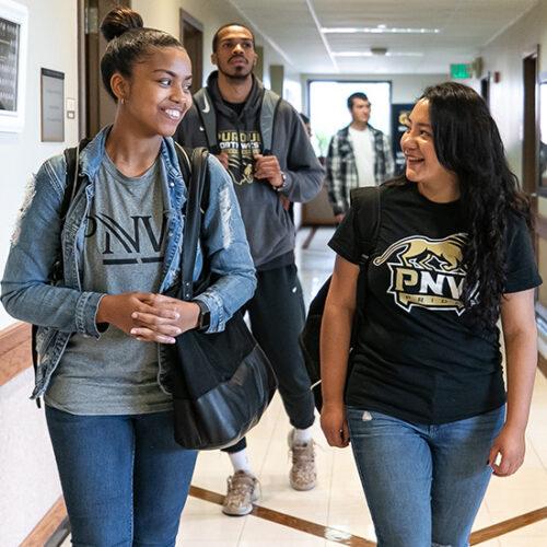 PNW students walk down a hallway
