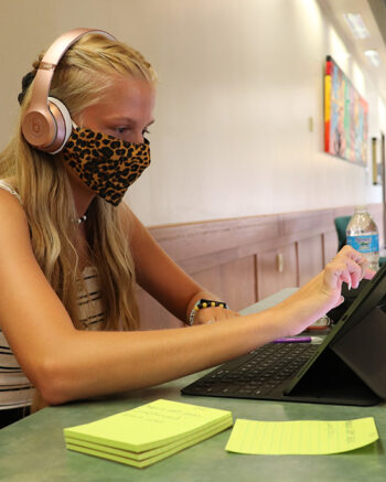 A PNW wears a mask and works on a laptop