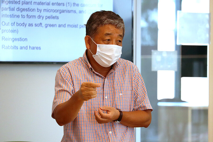 A professor wears a mask while teaching in the classroom.