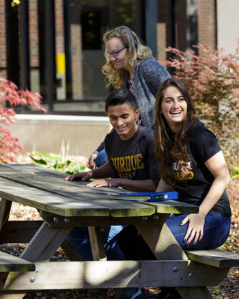 Students sitting outside on bench