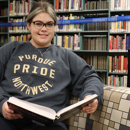 PNW student Victoria Archuleta reads a book in the library