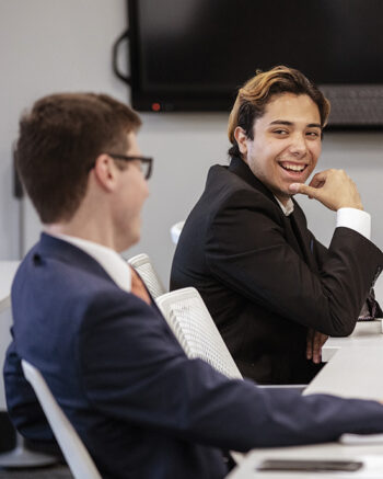 Students in suits laugh in PNW's Professional Selling Lab