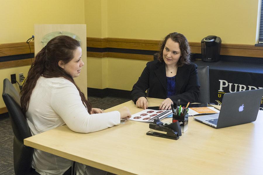 2 Students sitting on desk going over presentation