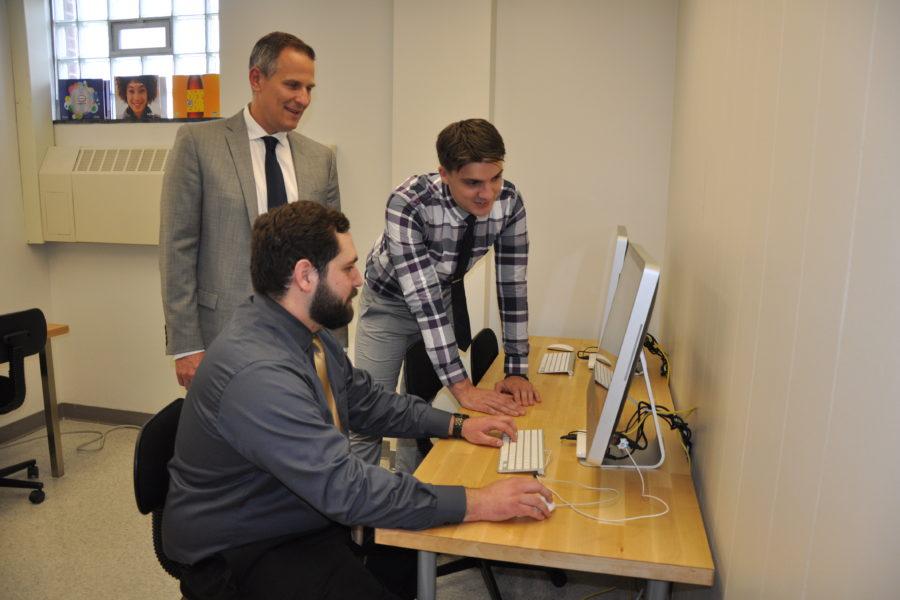 Staff and students sitting around computer