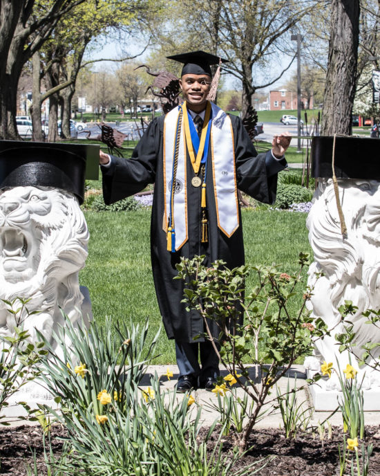 Student posing outside next to lion statues at graduation