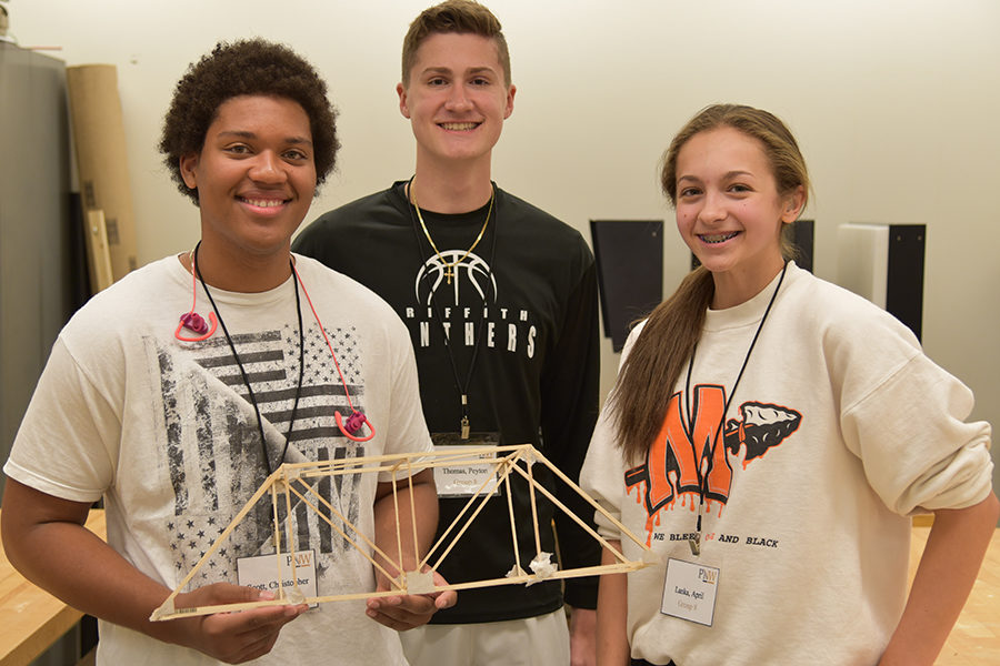three high school students holding wooden bridge project and summer engineering camp