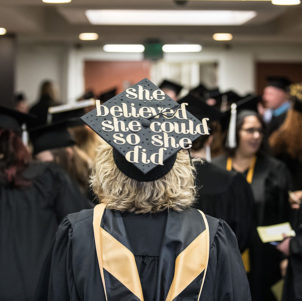 "A PNW graduate in a crowd. Her cap reads ""She believed she could so she did."""