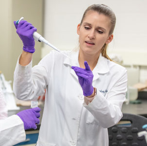 Professor Lindsey Gielda works with students in a lab.