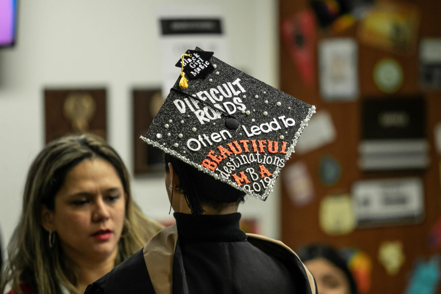 "A students commencement cap says ""Difficult roads often lead to beautiful destinations: MBA."""