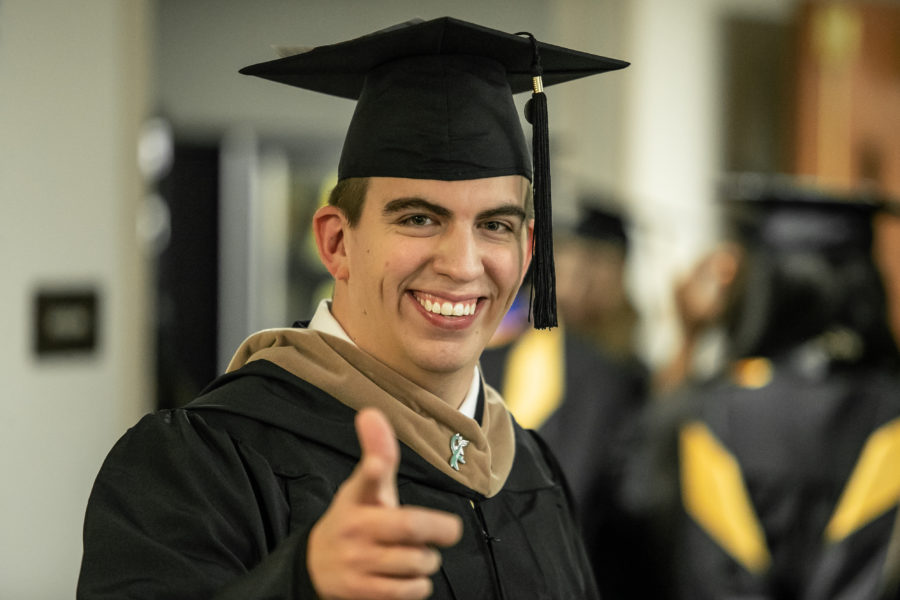 A student gives a thumbs up in his cap and gown.
