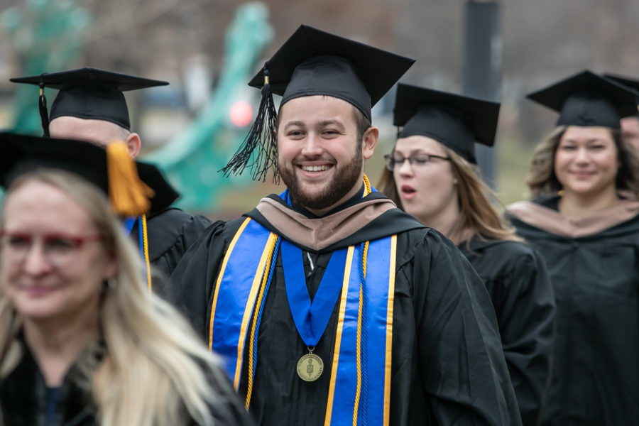 Students march toward commencement.