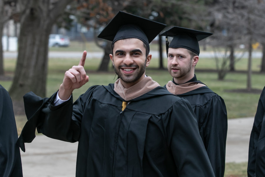 "A student raises a ""Number One"" finger on the march to commencement."