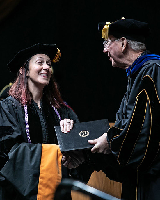 A student receives her diploma from Chancellor Keon