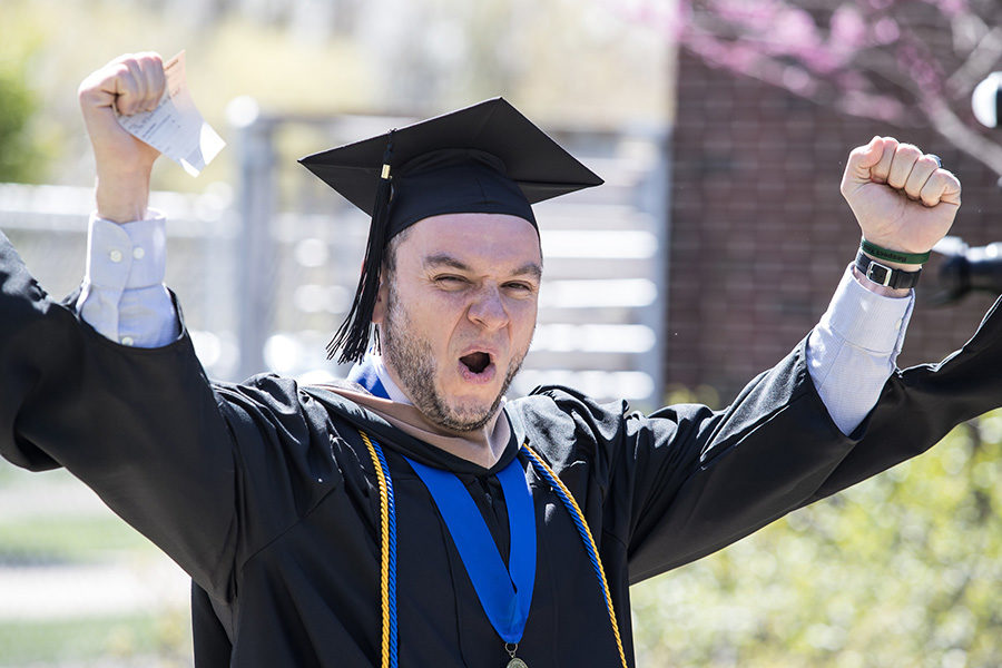 A graduate raises his arms to celebrate.