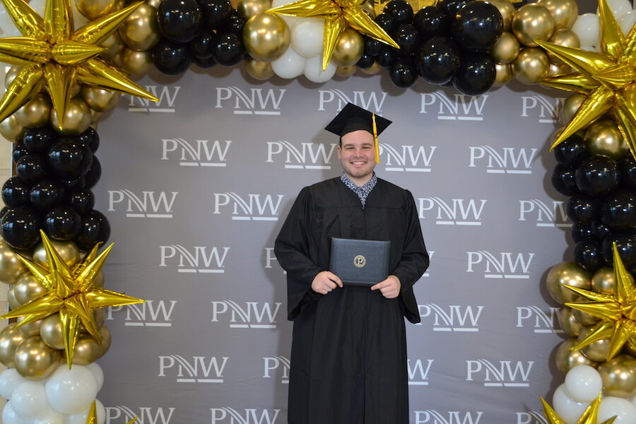 Student is pictured in front of logo and balloons.