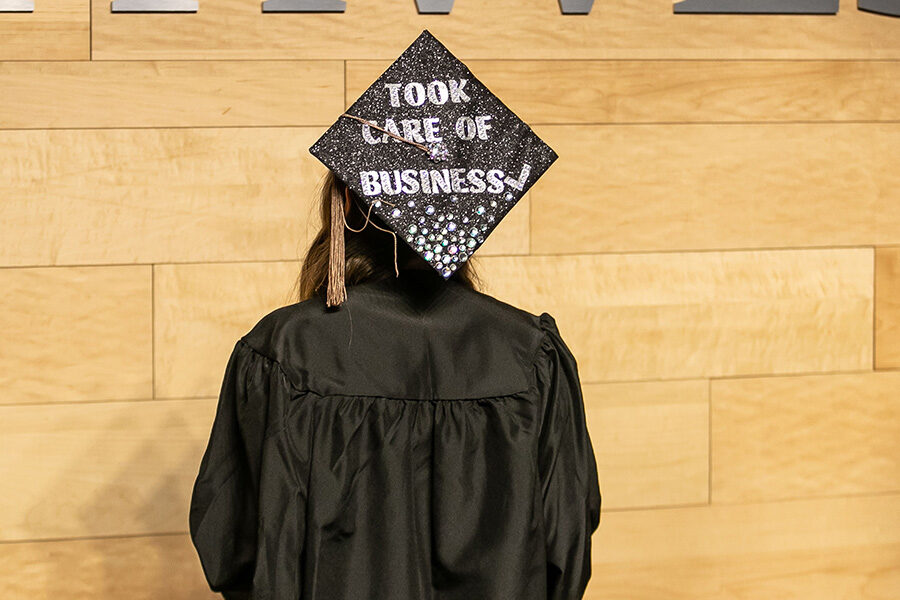 "A PNW grad with their back to the camera--their cap reads ""Took Care of Business"""