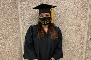 A PNW student in graduation regalia and a mask.