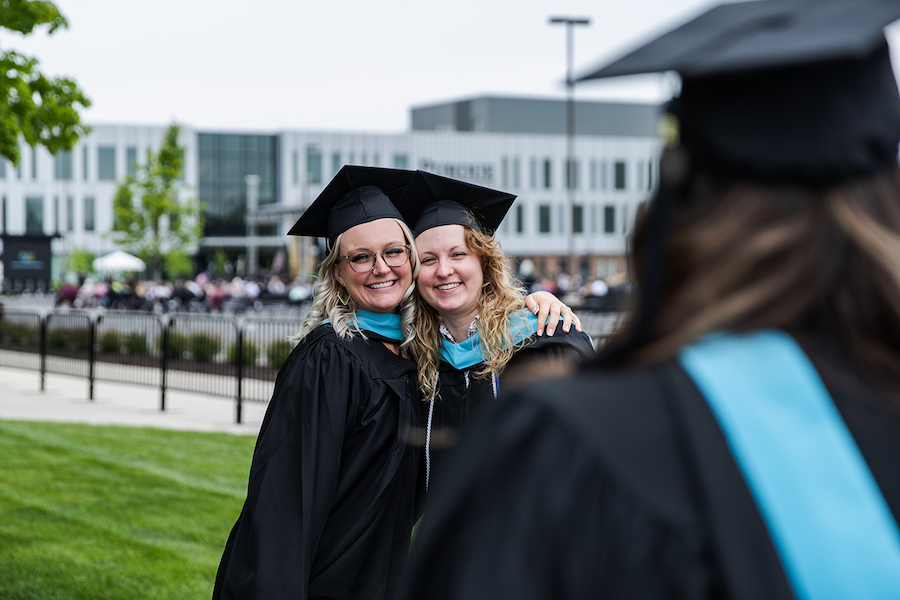 Grads are hugging at commencement.