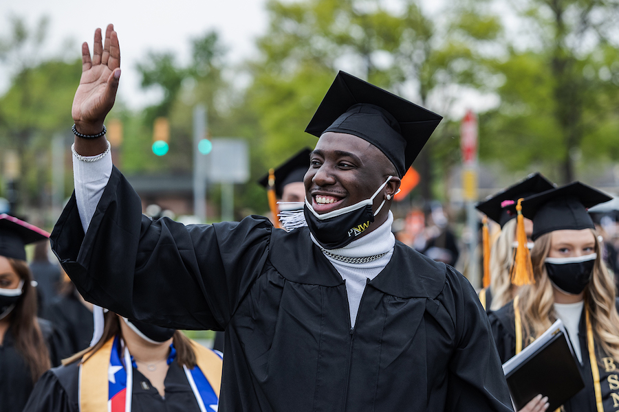 Student waving at commencement.
