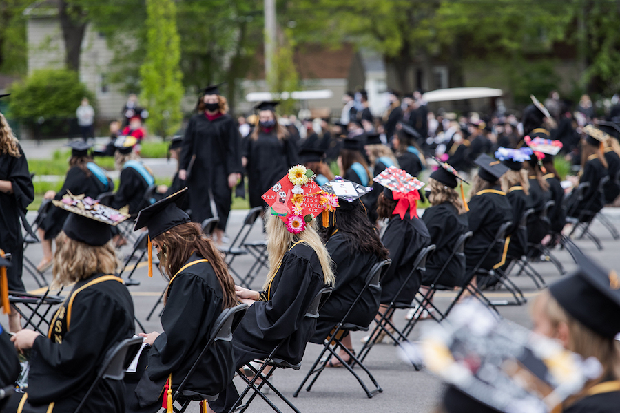 Students are pictured sitting at commencement.