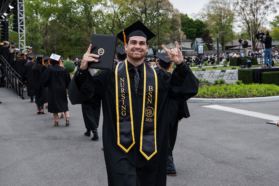 A graduate celebrates at spring 2021 commencement.