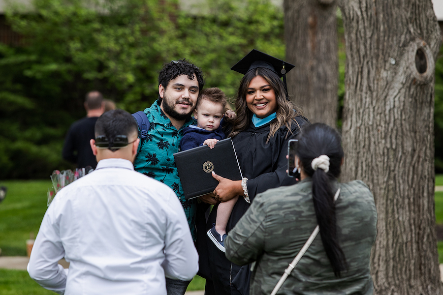 A graduate poses with her baby.