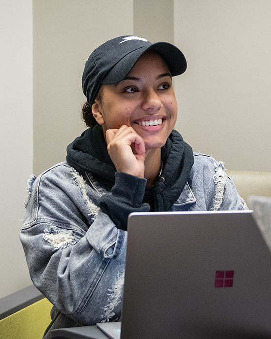 Student on laptop is pictured.