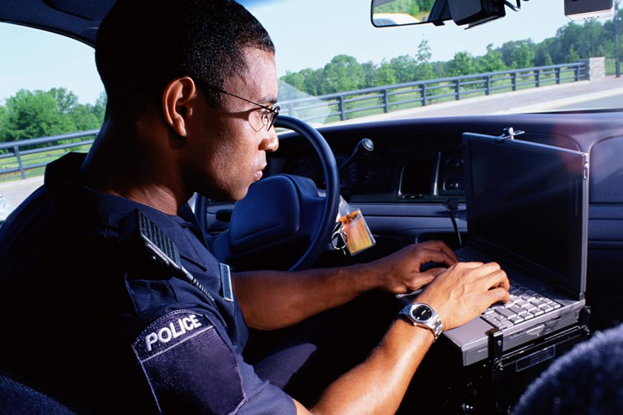 First responder working on computer in car