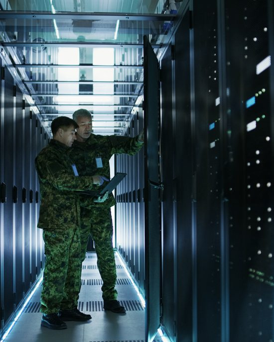 In Data Center Two Military Men Work with Open Server Rack Cabinet. One Holds Military Edition Laptop
