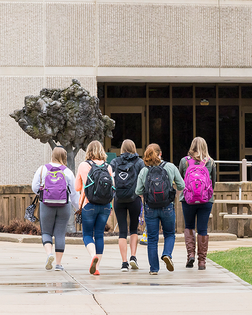5 students with backpacks walking into Build on Westville Campus