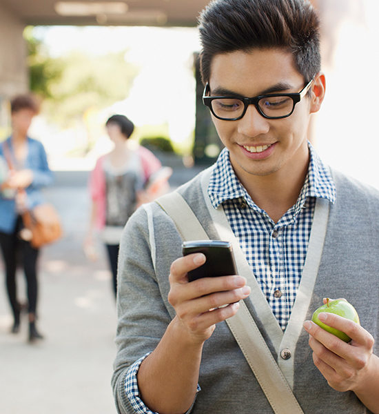 Student texting and holding an apple