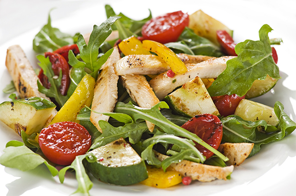 Chicken salad with rocket and vegetables close up