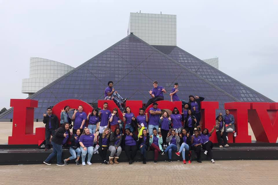 Students posed on and around a sign outside of the Rock and Roll Hall of Fame