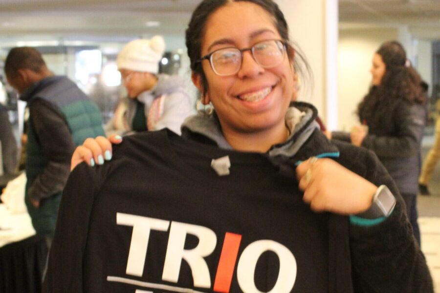 Female Upward Bound student holds a black TRIO shirt in front of her chest at the University of Wisconsin Milwaukee TRIO Day event.