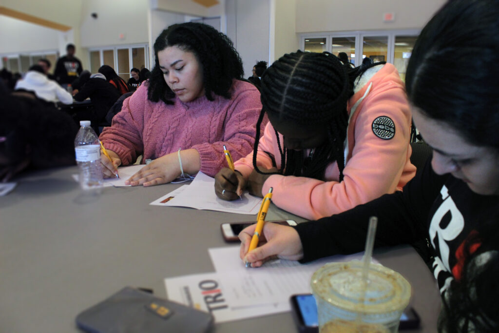 Three Upward Bound students participating in a writing activity for TRIO Day on the University of Milwaukee Wisconsin campus.