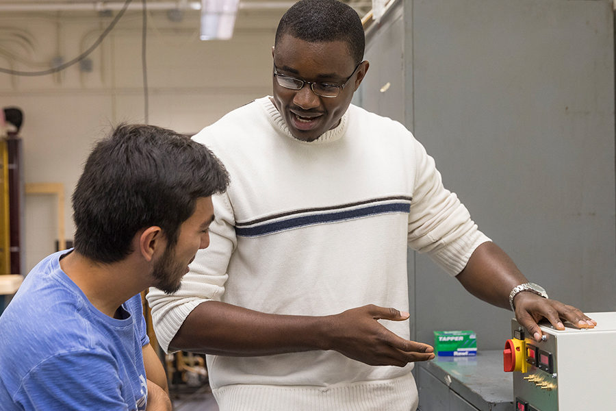 Professor showing a student a piece of equipment