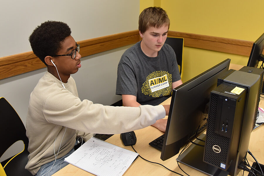 two students working on computer project at artificial intelligence summer camp