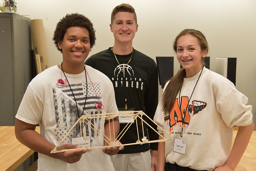 three high school students working on team wooden bridge project at pnw summer engineering camp