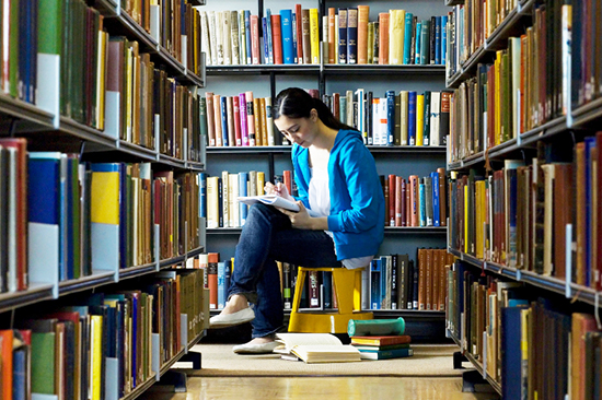 Student surrounded by books in a library