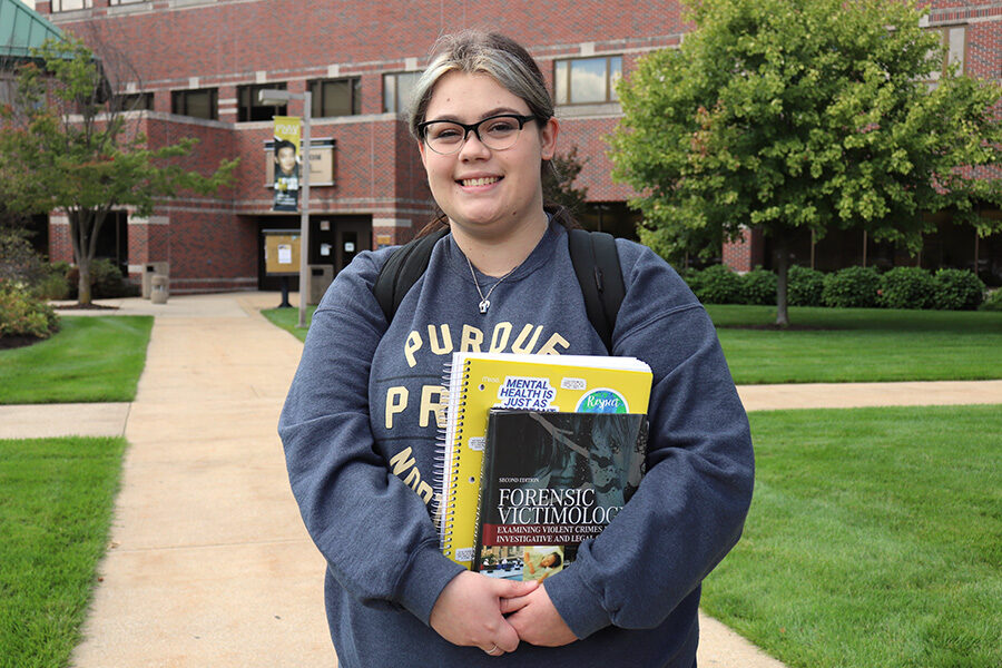 PNW student Victoria Archuleta poses with textbooks outdoors on campus.