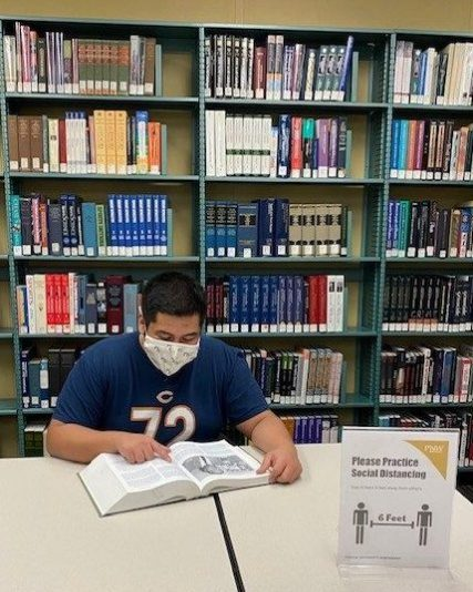 student reading a book wearing a face mask