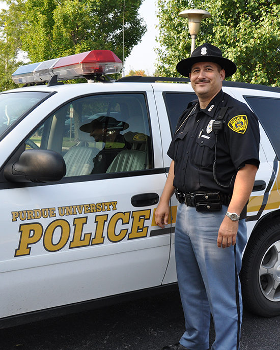 Police Officer John Mucha with a Police car