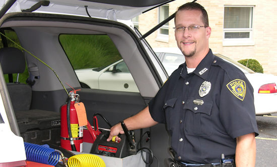 Police officer getting ready to jump start a car