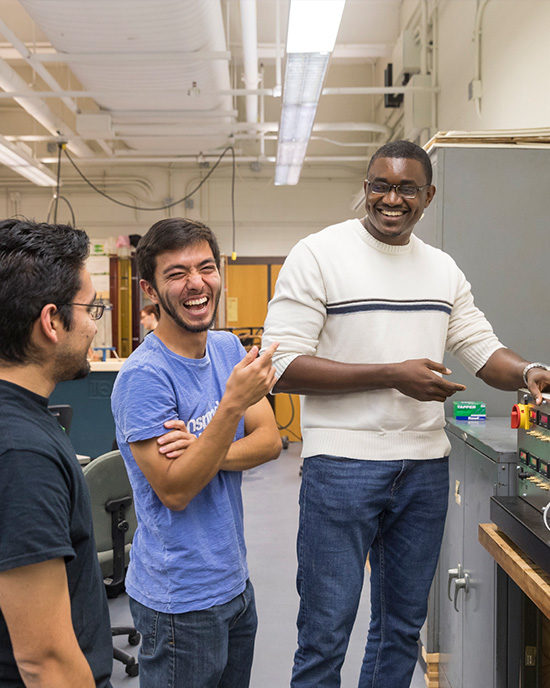 two students and professor laughing in engineering lab