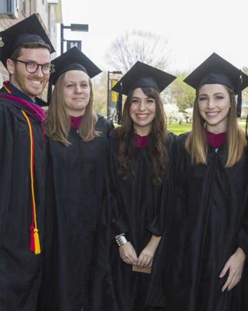 four graduates posing for camera