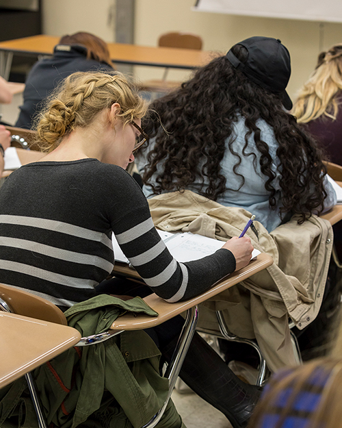 Student in classroom taking notes