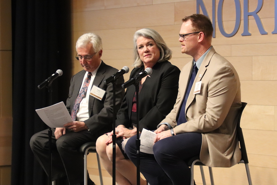 Three team members on stage discuss the Society of Innovators.
