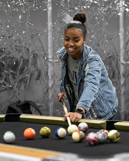 A PNW student plays pool.
